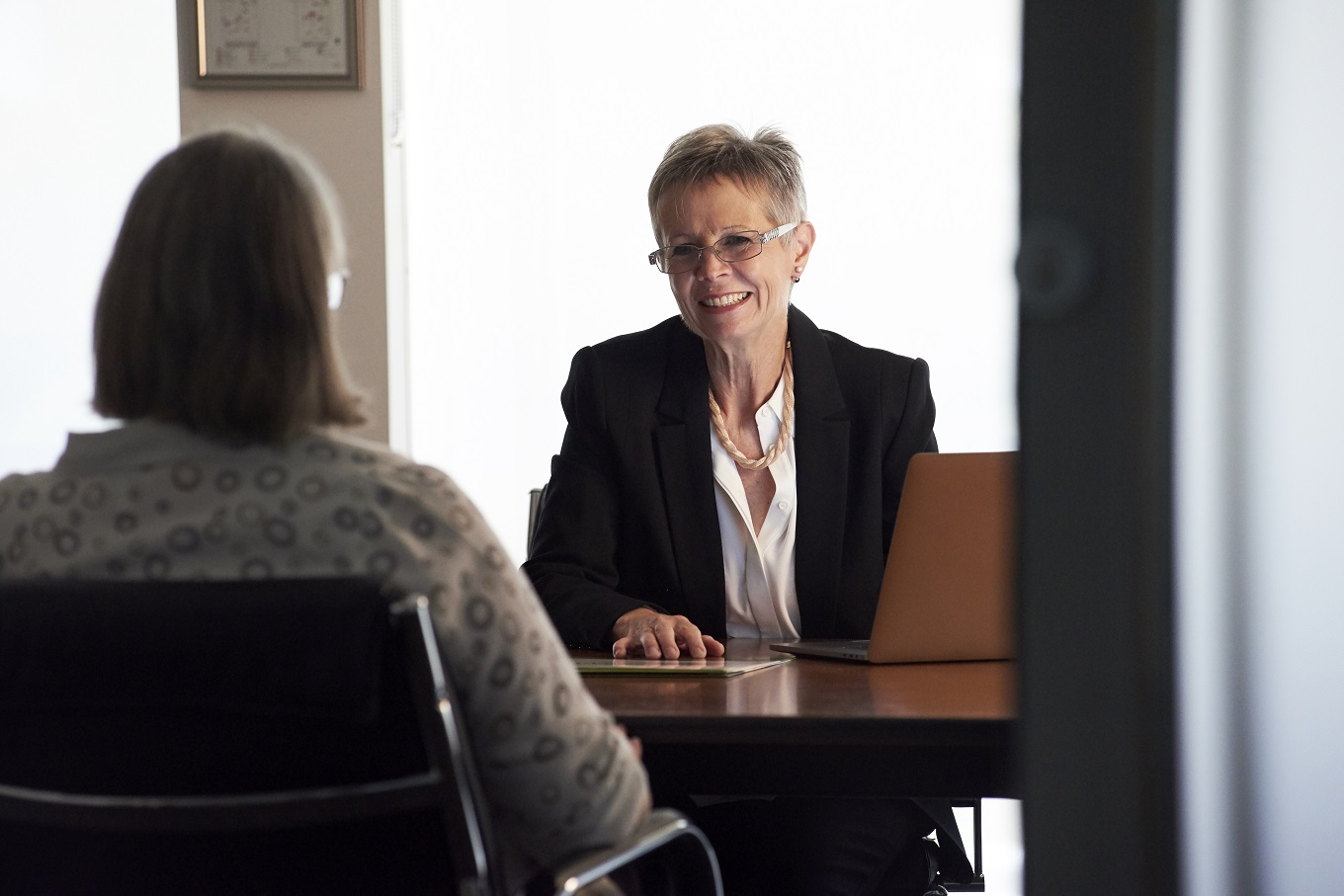 image of two women in a business meeting, smiling